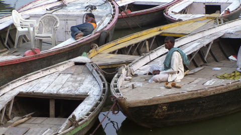 Man eating on docked boats in the Ganges River Footage