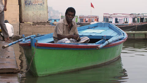 Tight shot of a man in a colorful boat waits by the wharf. Shot from a low angle Footage