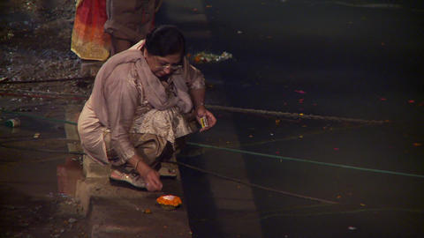 Indian woman lighting relighting a floating candle Footage