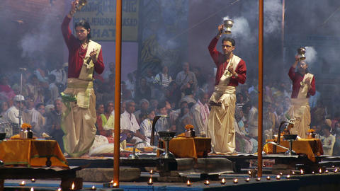 Three men swinging incense burners, making an incense offering to the Ganges riv Footage