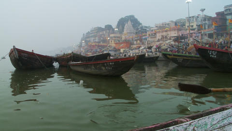 Shot passing several moored boats on the Ganges. City in the background Footage