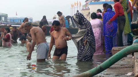 Couple enter Ganges River other pilgrims, bathers, around them Footage