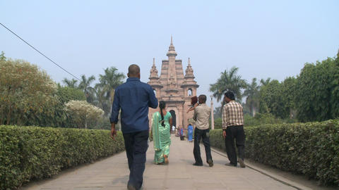 Group walking towards Buddhist temple Live Action