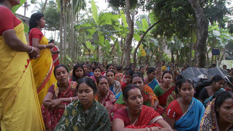 A few Indian women standing in front a of a large group of women sitting on the  Footage