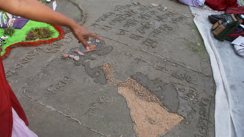 Indian woman pointing to a drawing on the ground Footage