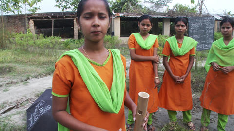 Four Indian women outdoors in matching orange and green clothes Live Action