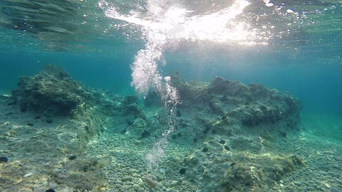 Underwater shot of a rock landing in water Footage