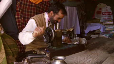 Man with pink measuring tape around his is sewing clothes on antique sewing mach Footage