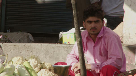 Man vendor in pink shirt sitting by cauliflower Footage