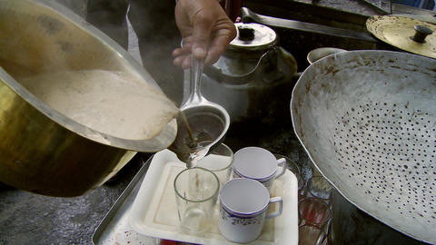 Man pouring chai tea into cups Footage