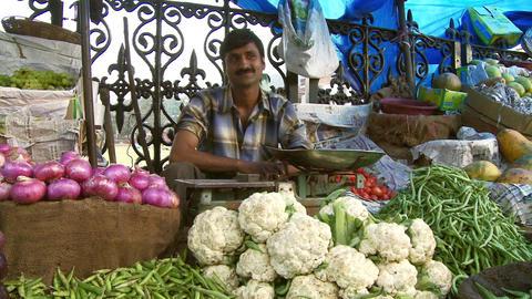 Male vendor selling vegetables cauliflower, potatoes, peas outdoors Live Action