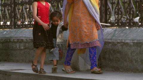 Women holding two girls hands walking down street in India Live Action