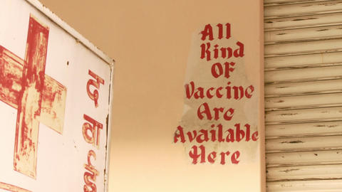 All kinds of vaccines are available here sign next to red cross sign Live Action