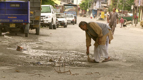 Old man sweeping in streets of India Footage