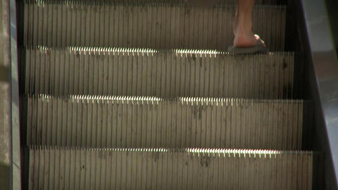 Tight shot of an escalator as a guy walks up them Live Action