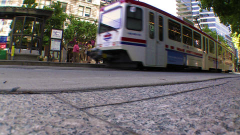 Low angle shot of a street as a tram and a car drive by Footage