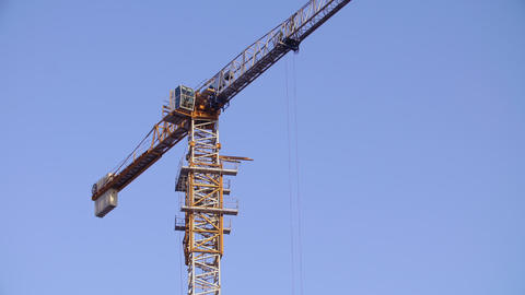 Tower crane working on construction site sunny day clear blue sky sunny day Live Action