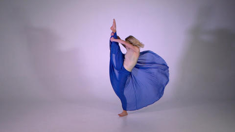 A blonde girl doing a leg split and jumping on one leg in studio Live Action