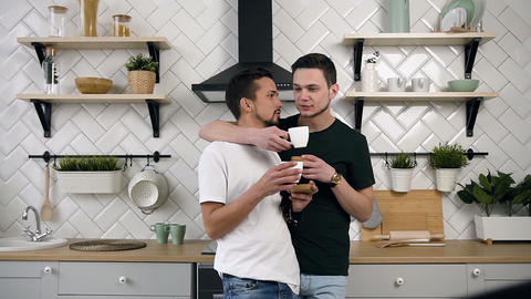 Handsome gay couple are hugging and drinking coffee. Gay relationships concept Live Action