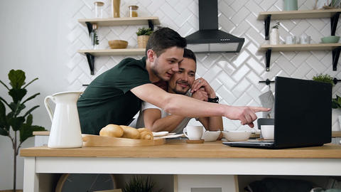 Lovely caucasian gay couple, homosexual couple, are hugging and having breakfast Footage