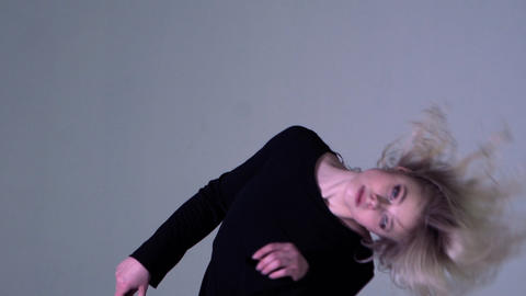Blonde girl dancing with wind in hair indoor in slow motion Footage