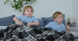 Two children watch an exciting TV show on TV. Two brothers are watching TV Footage
