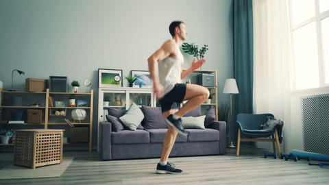 Professional runner exercising at home running on the spot doing cardio training Footage