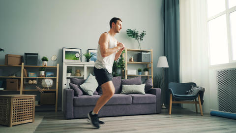 Handsome young guy exercising at home doing sports exercises for legs and body Live Action