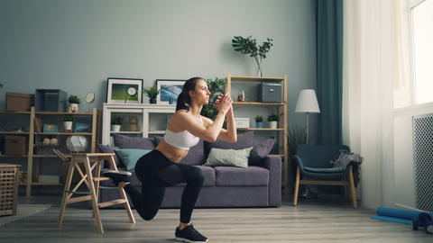 Muscular young woman is doing squats indoors concentrated on physical exercise Footage