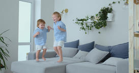 Two brothers of little boys are jumping on the couch and having fun. Joy Footage