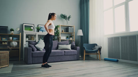 Pretty female student doing sports at home crouching... Stock Video Footage