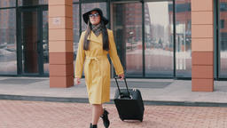 stylish girl with long hair in a hat and glasses comes with luggage Footage