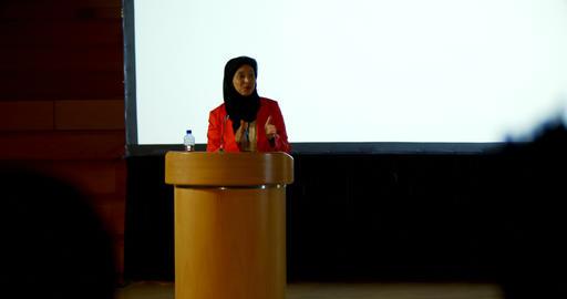 Mature Caucasian hijab businesswoman speaking at podium in auditorium 4k Live Action