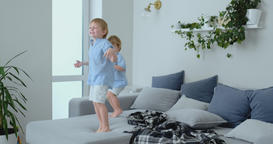 Two little boys jumping on the couch and having fun. Joy, laughter and fun at Footage
