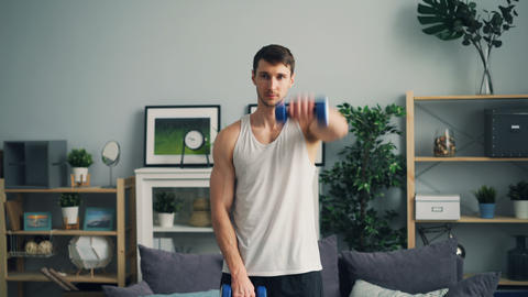 Handsome sportsman working out with dumbbells raising arms practising in house Live Action