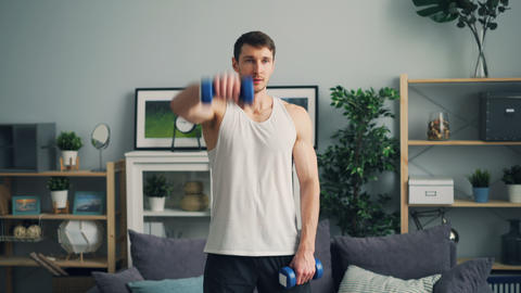 Muscular guy training with heavy dumb-bells in apartment raising arms breathing Live Action