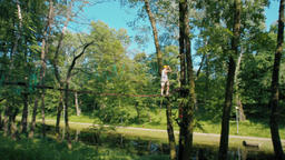 Man in Adventure High Rope Park Doing Climbing Exercises on Unstable Bridge Footage