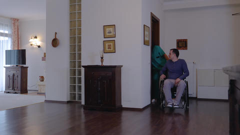 Care worker with young man in wheelchair at home Stock Video Footage