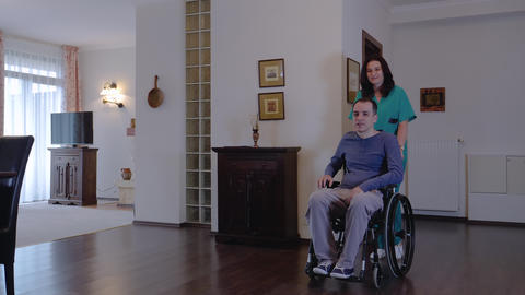 Care worker with young man in wheelchair at home Live Action