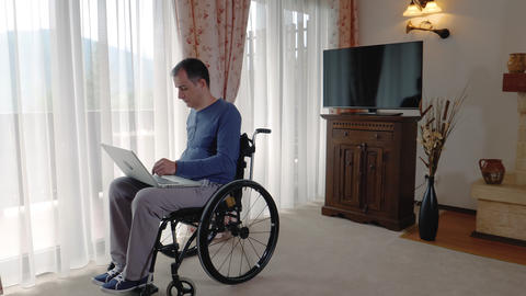 Young man in wheelchair working at laptop computer at home Footage