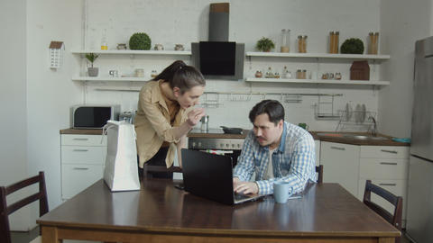 Wife scolding husband gaming on laptop in kitchen Footage