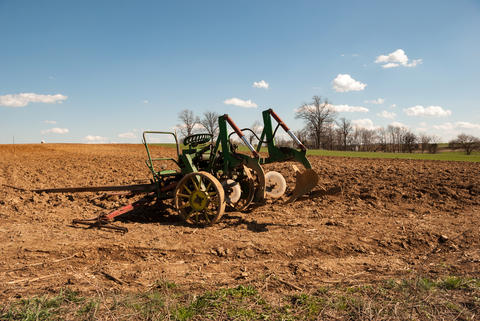 Amish Farm with Old Farm Equipment sitting in the Field フォト