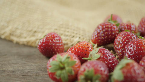 Close up of strawberries heap on wooden table, pan shot Live Action