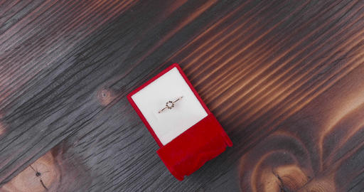Engagement ring in red case on vintage wooden background Live Action