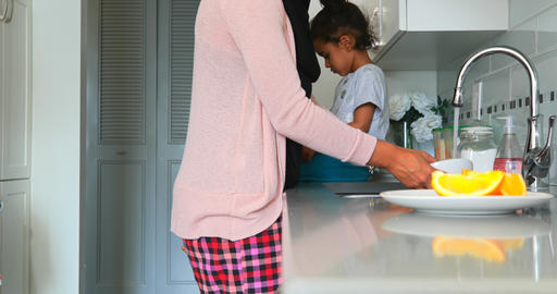 Young mother washing dishes in kitchen at home 4k Live Action