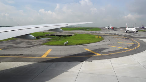 The plane turns on the runway, view from the window. Other planes at the airport Live Action