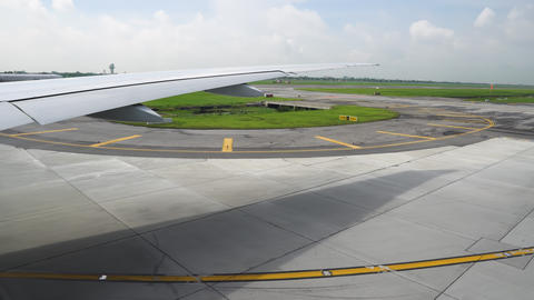 The runway under wing of aircraft. Airplane moving on the runway in terminal of Live Action