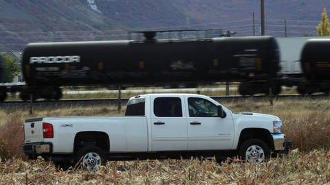 Chevy pickup in a cut corn field as a train passes behind Footage