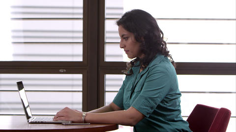 Panning shot of woman using computer with green screen Footage