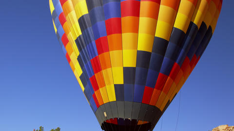 Tilting shot of a colorful hot air balloon with passengers aboard, preparing to  Footage